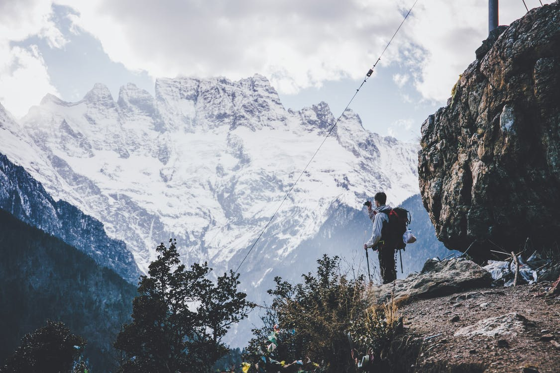 Side view of male alpinist with backpack and trekking sticks standing on edge of cliff and enjoying view of highland