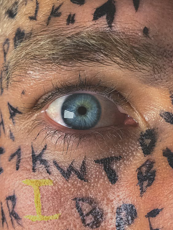 Crop male with wide opened blue eye and Latin alphabet letters painted on face skin staring at camera
