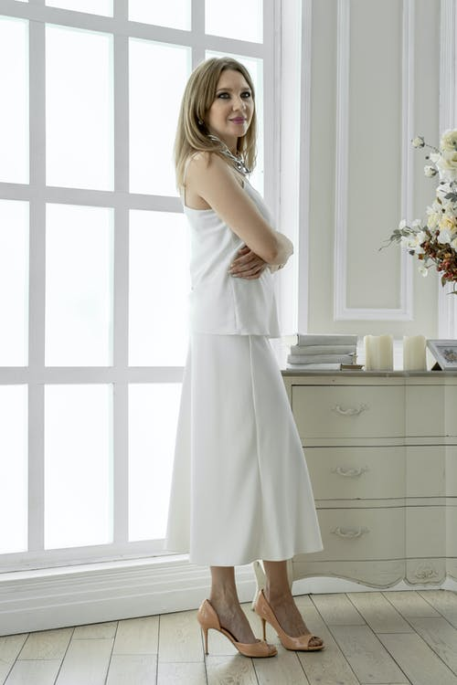 Attractive woman in white dress standing in light bedroom