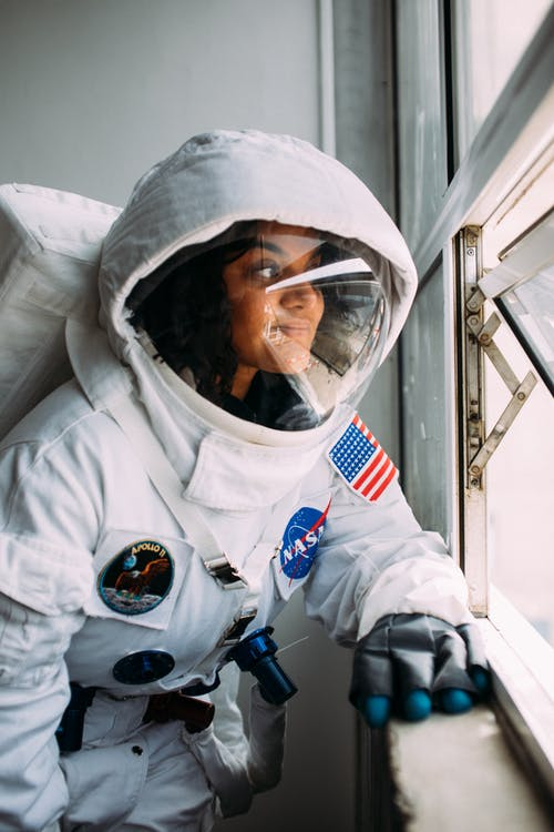 Woman Wearing An Astronaut Costume Looking Out The Window