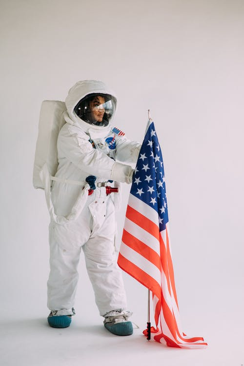 Woman In A Space Suit Holding A Flag