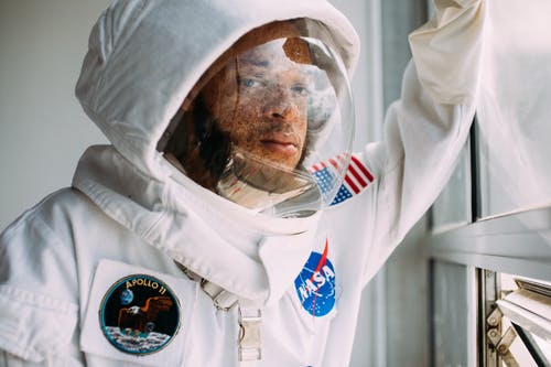 Man In A Space Suit Leaning On A Window