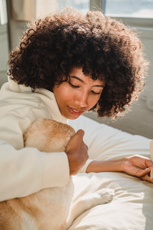 Black woman with Afro hairstyle hugging dog