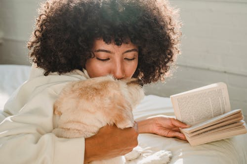 Black woman caressing with dog while reading book