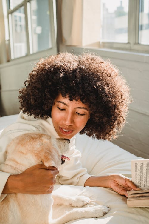 Black woman hugging dog while reading book in bedroom