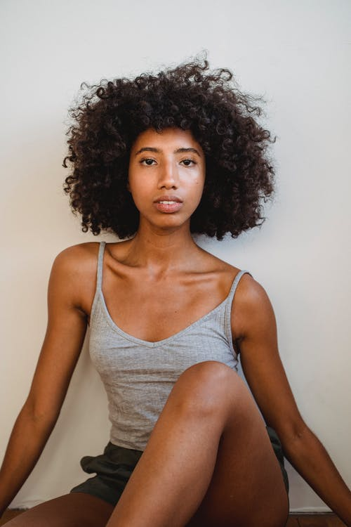 Black woman with curly hair against white wall