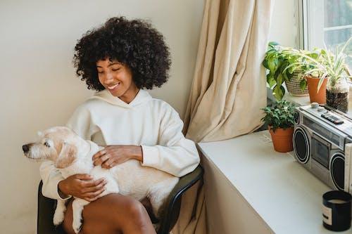 Mulher Negra Sorridente Abraçando Um Pequeno Animal De Estimação Sentado Perto Da Janela