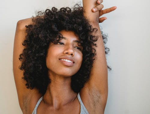 Happy African American female with curly hair and hands raised smiling and looking away
