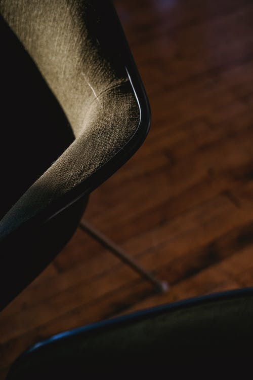 From above of black stylish modern chairs in dark room on wooden surface