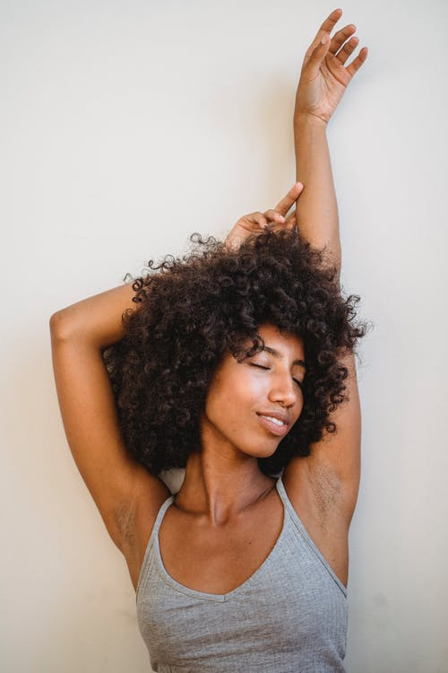 Young African American female smiling and raising hands while posing with eyes closed