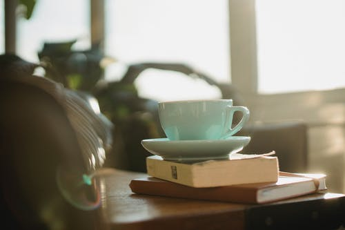 White ceramic cup of tea with plate and worn book with notebook placed on table