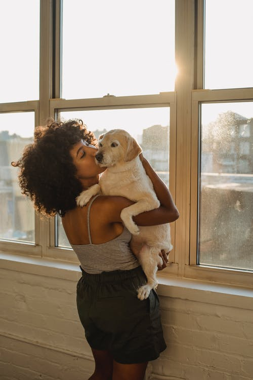 Young African American female standing near window on balcony and kissing and hugging dog