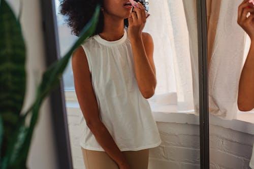 Crop black woman applying lip gloss against mirror