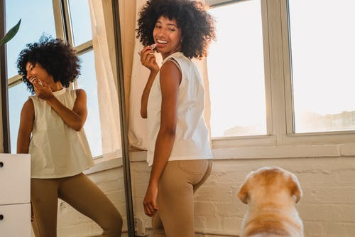 Side view of glad ethnic female with Afro hairstyle making up lips in front of mirror while looking at dog in house