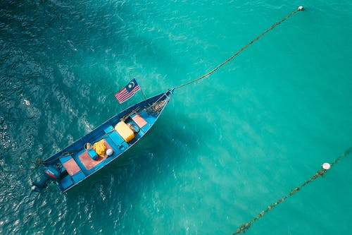 From above of blue small boat with flag of Malaysia floating on water of sea at daytime