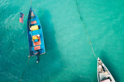 High angle of colorful small boats with motors moored in clear turquoise water of ocean in sunny day