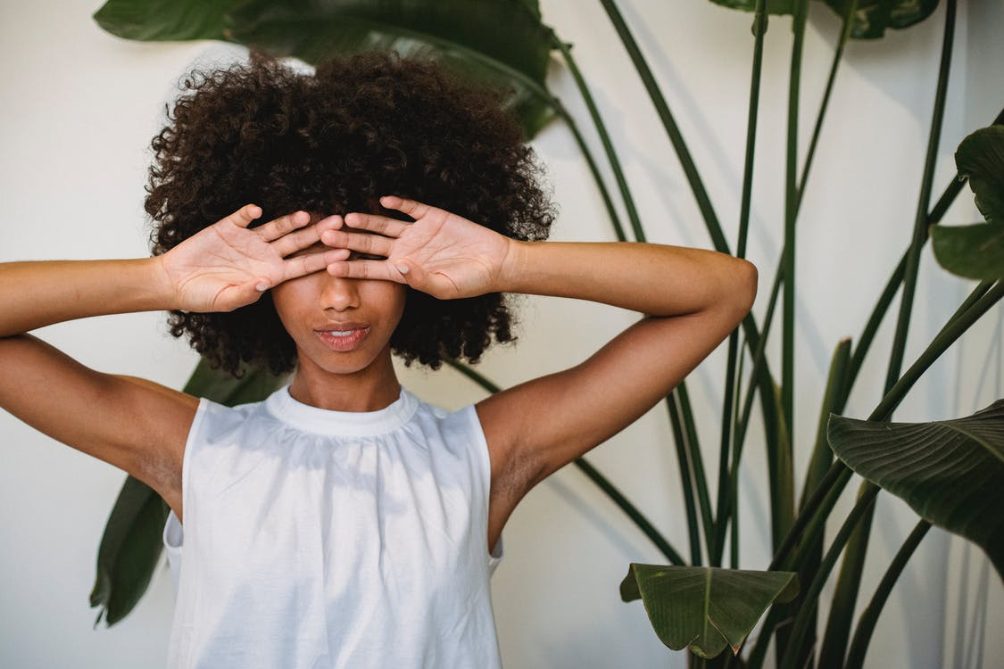 African American female with Afro hairstyle standing near green plant and hiding eyes behind hands