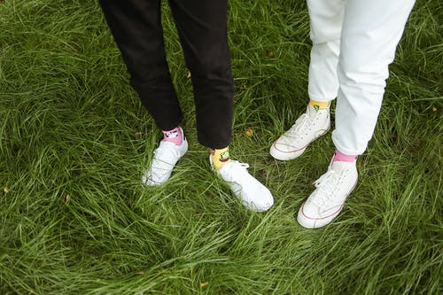 Two People Wearing Black and White Pants Standing on Grass