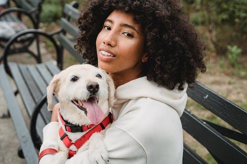 Black woman hugging dog while sitting on bench
