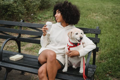 Relaxed black woman drinking coffee near dog