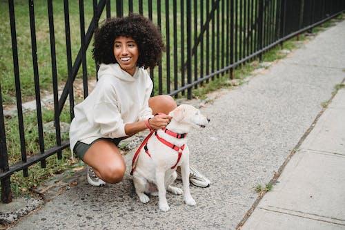 Positive black woman on sidewalk with dog