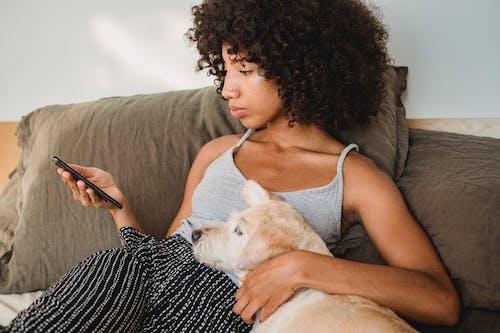 Crop Femme Noire Regardant Smartphone Tout En Embrassant Chien Sur Le Lit