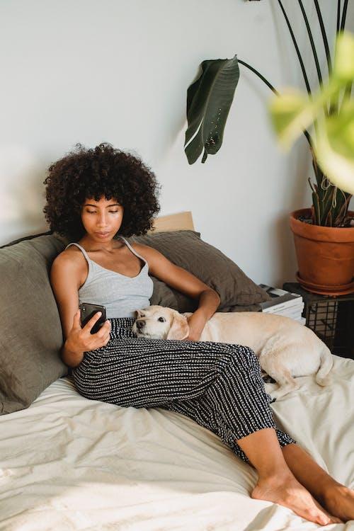 Người Phụ Nữ Dân Tộc Xem điện Thoại Thông Minh Với Con Chó Trên Giường