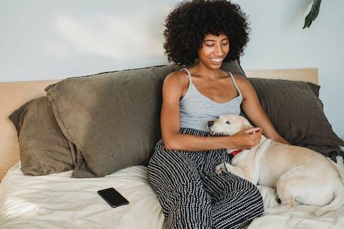Веселая черная женщина гладит собаку на уютной кровати