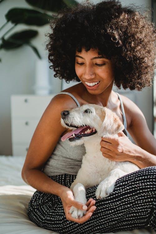 Счастливая черная женщина обнимает собаку в спальне