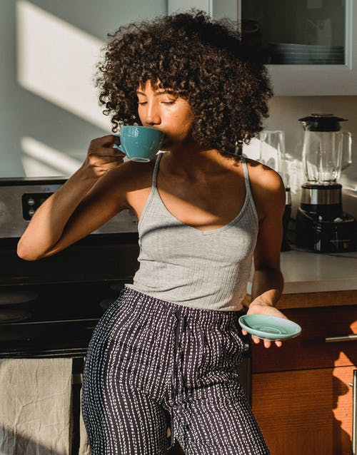 Woman Enjoying A Cup Of Coffee In The Kitchen