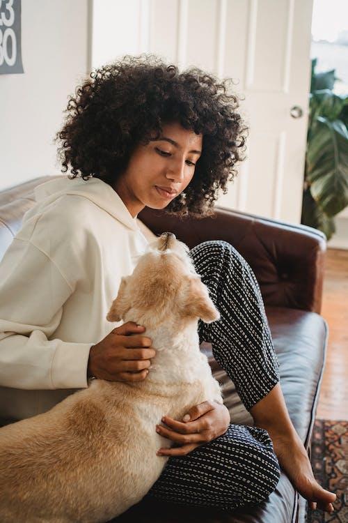Black female hugging with dog in living room