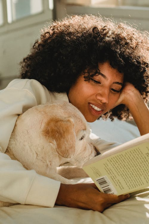 Woman Reading A Book With A Dog