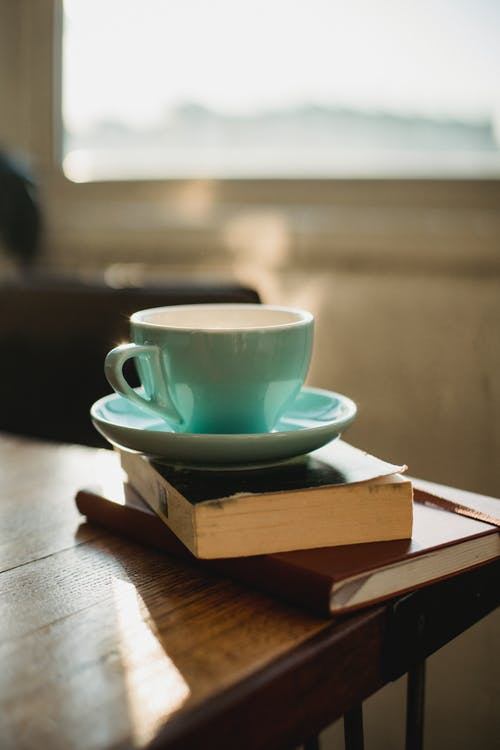 Cup of fresh aromatic coffee and books on wooden table against window at home