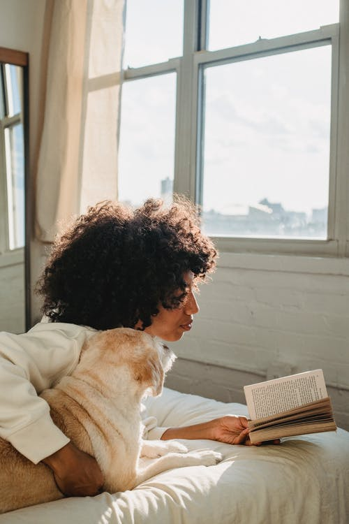 Black woman embracing dog while reading