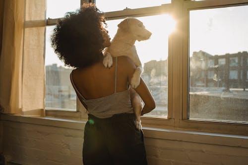 Black woman holding dog near window