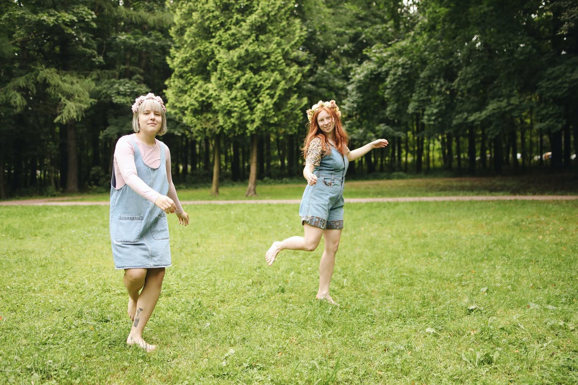 Woman in White Shirt and Blue Denim Shorts Holding Girl in White Shirt on Green Grass