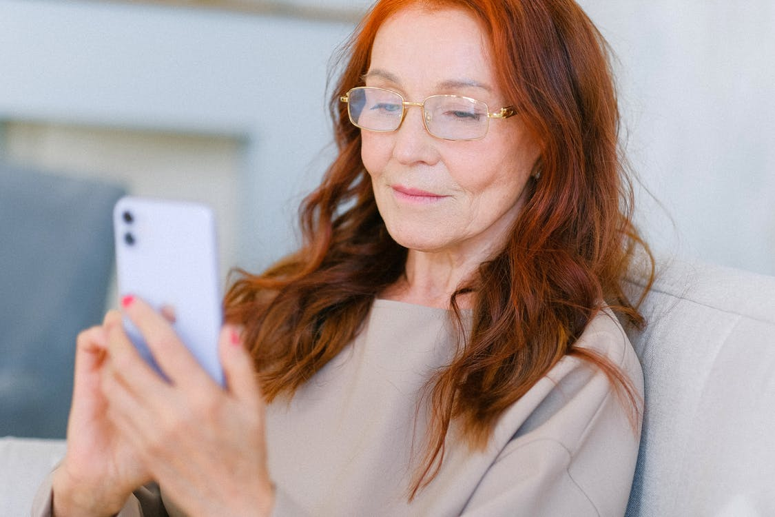 Aged female with red hair in eyeglasses looking at screen of smartphone and making online video call on blurred background