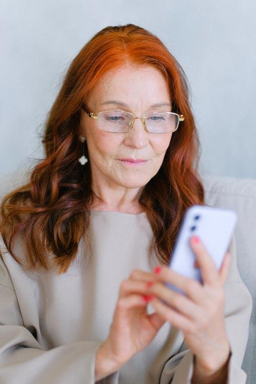 Elderly redhead woman in eyeglasses texting on smartphone