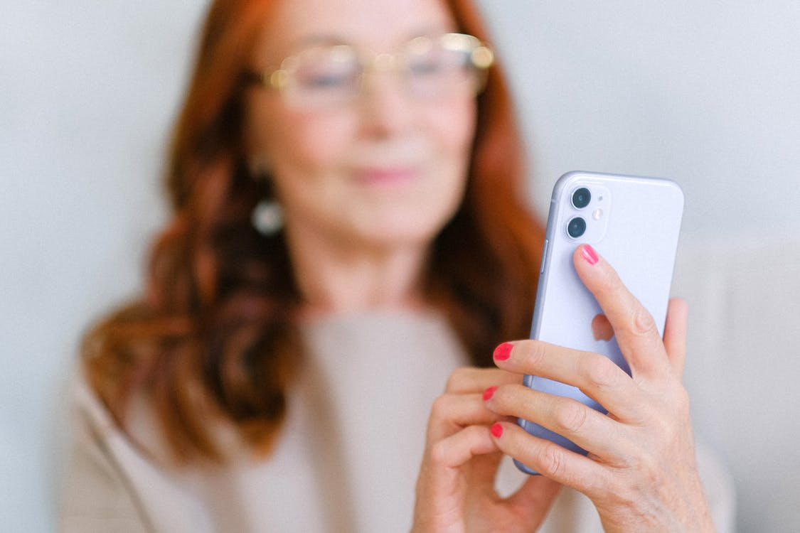 Crop aged redhead female in eyeglasses using contemporary mobile phone while surfing internet in soft focus