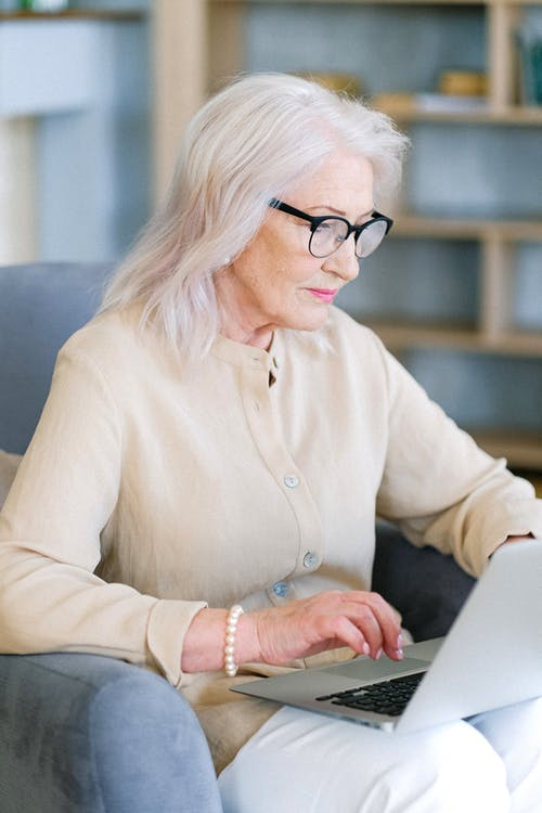 Aged woman in eyeglasses surfing internet on laptop