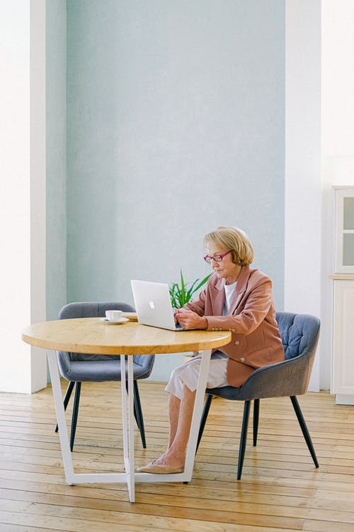 Woman in Blue Long Sleeve Shirt Sitting on Chair Using Macbook