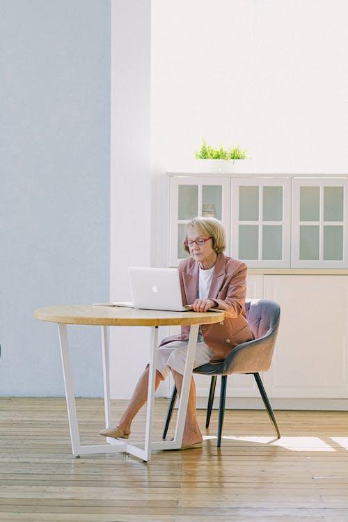 Full body of elderly female in eyeglasses improving important report while using netbook at table in modern room