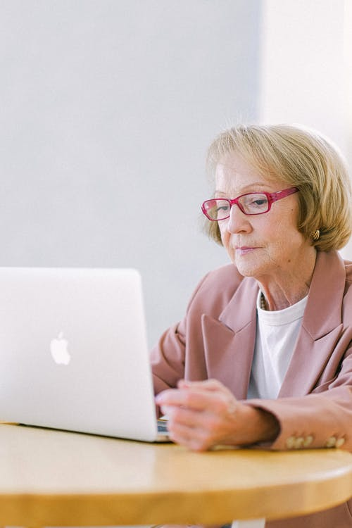 Serious senior woman creating business project on laptop