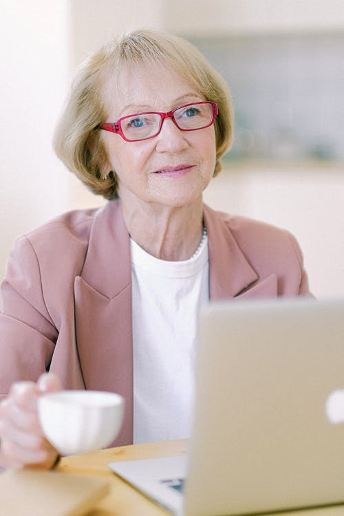 Senior woman with cup working on remote job on laptop