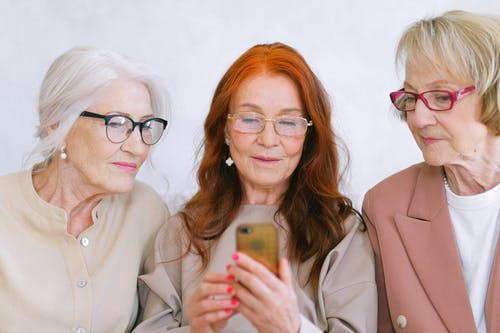 Group of elderly fashionable elegant women surfing internet on mobile phone together