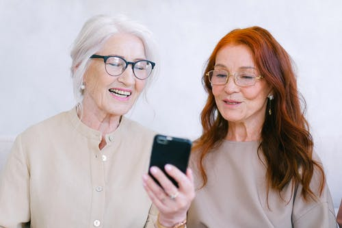 Cheerful aged women smiling and watching video online on smartphone