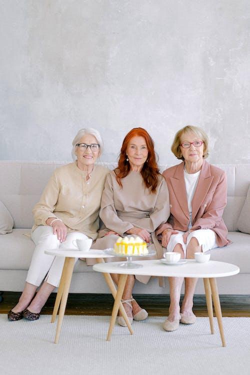Aged elegant women having teatime with sweet cake