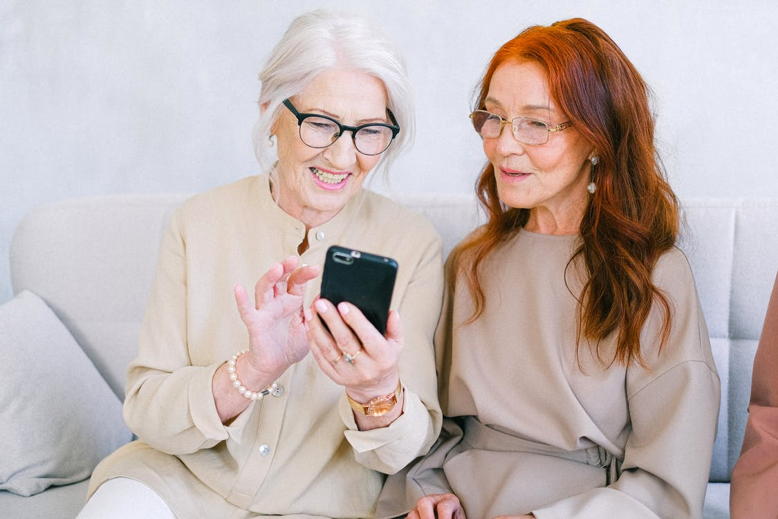 Happy elderly elegant trendy women looking at screen of mobile phone and shopping online while resting on sofa