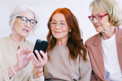 Happy aged women in eyeglasses looking at screen of smartphone