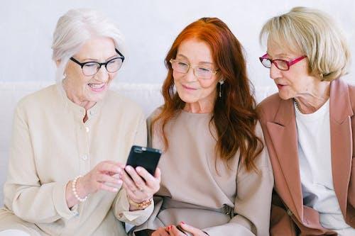 Senior happy women watching video online in smartphone